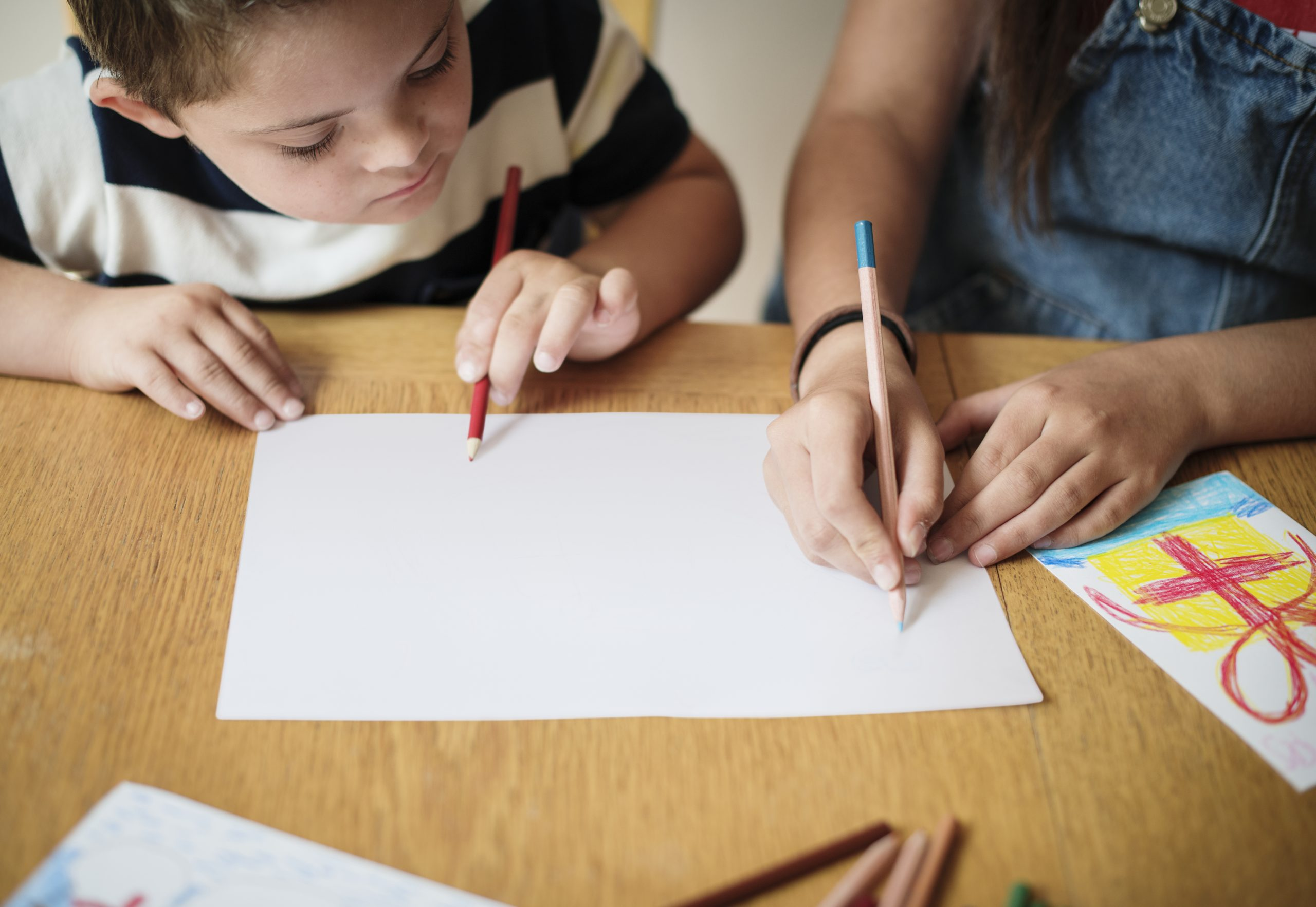 two kids drawing at a table